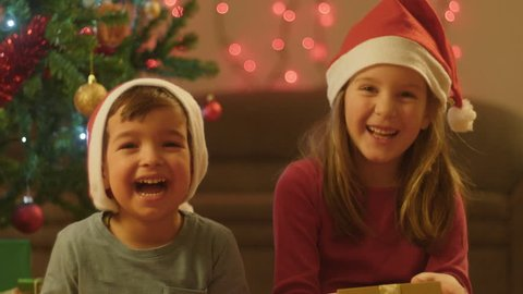 Close-up of an adorable boy and girl having fun on the living room floor on Christmas evening.