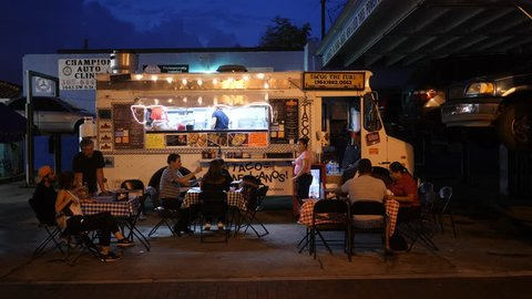 Miami, August 2017. Taco truck on sidewalk with people eating at little tables in Cuban neighborhood Little Havana. Night time.