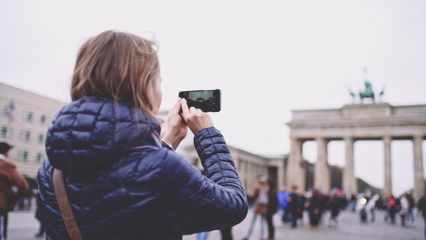 Woman Taking Pictures of Brandenburg Gate in Berlin with SmartPhone. SLOW MOTION. Young woman tourist with cellphone photographing Brandenburger Tor. Travel in Germany.