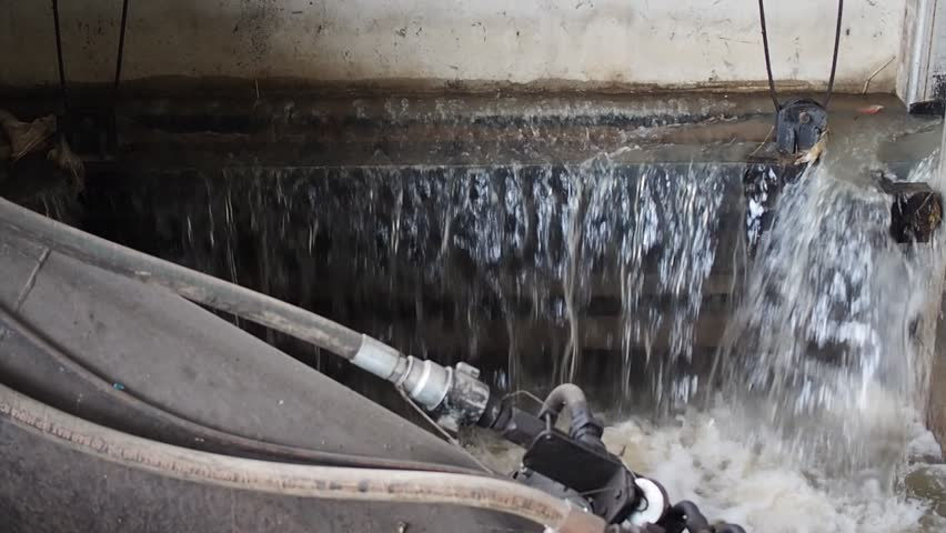 River water overflow falling from watergate cement wall, with hydraulic steel pumping pipe with pressure parameter printed
