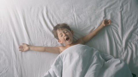 Little boy stretching in bed after wake up