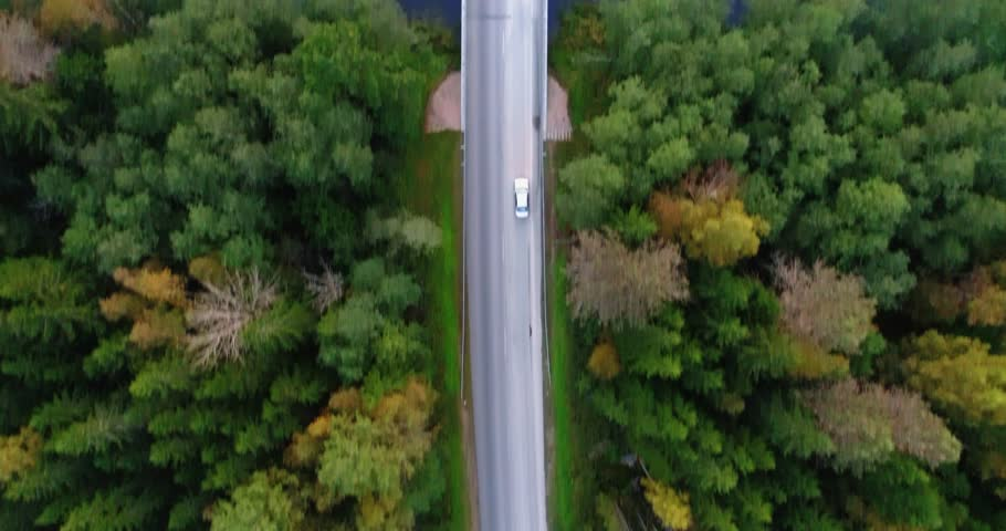Sky view of autumn road with cars. Aerial view country road in autumn forest. Autumn forest and highway road drone view. Autumn car road in forest top view. Aerial landscape