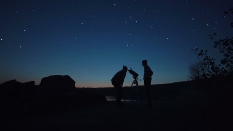 Black silhouettes of people looking through telescope on stars in dark twilight on shore.