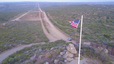 CIRCA 2010s - U.S.-Mexico border - The American flag flies over the U.S. Mexico border wall in the California desert as a border patrol passes beneath.