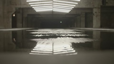 4k shot of white fluorescent lighting turn on and off and reflecting in the water or puddle in industrial building. Many neon lights blinking and flashing on the ceiling.