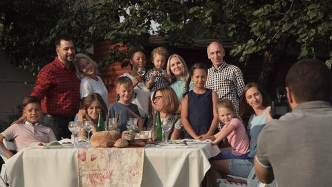 Cheerful family standing at table in garden and posing for photo.