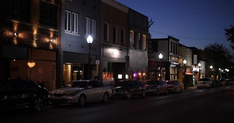 A nighttime establishing shot of businesses on a typical Main Street in America. Pittsburgh suburb.	Building names and addresses obscured.  Day/Night matching available.