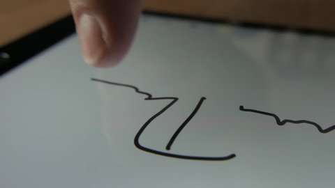 Man signing his name on a tablet screen. E-signature or digital signature.