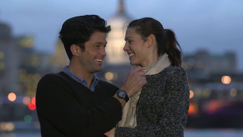 Attractive casually dressed couple enjoy an intimate moment overlooking the river Thames in London. It is evening time and the bright lights of the city can be seen across the water | Shutterstock HD Video #3140251