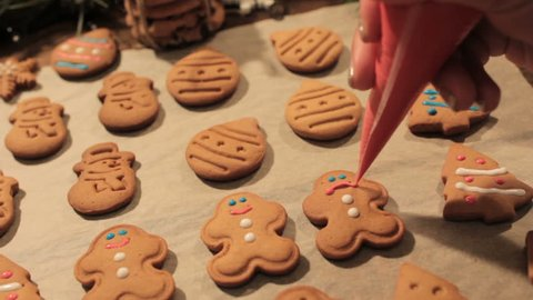 Decoration process of Christmas cookies. Close up woman garnishing homemade gingerbread men with sad smile near festive illuminate pine. Family culinary and traditions concept