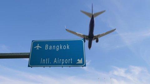 bangkok airport sign airplane passing overhead
