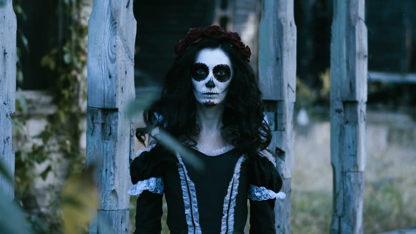 The Mexican Day of the Dead. The portrait of young woman with frightening skull make-up for Halloween on the background of wooden old house. 4K