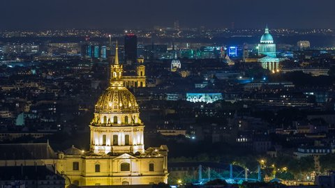 Aerial Night timelapse view of Paris City and Les Invalides shot on the top of Eiffel Tower observation deck. Evening illumination.