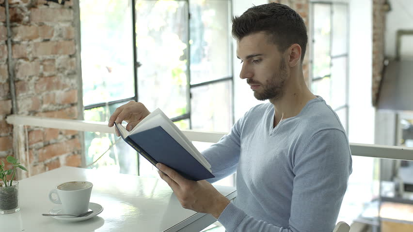 Handsome man in blue sweater reading book in the bistro and smiling to the camera, steadycam shot  | Shutterstock HD Video #31431331