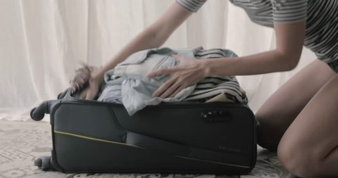Preparing bag for travel. Young woman packing and standing her bare knees on overfilled suitcase and closes a zipper on it on a white background curtains in the room