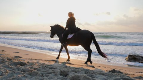 Young beautiful blonde woman in black clothing is carefully riding black horse on the seashore. Slow motion. Autumn sunrise or sunset on sea beach. Beautiful scene.