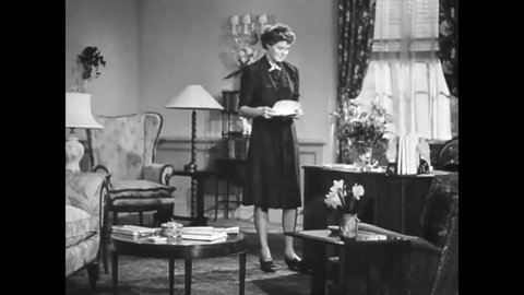 CIRCA 1943 - Actress Ingrid Bergman reads a letter asking about Swedes in America in the living room of her home.