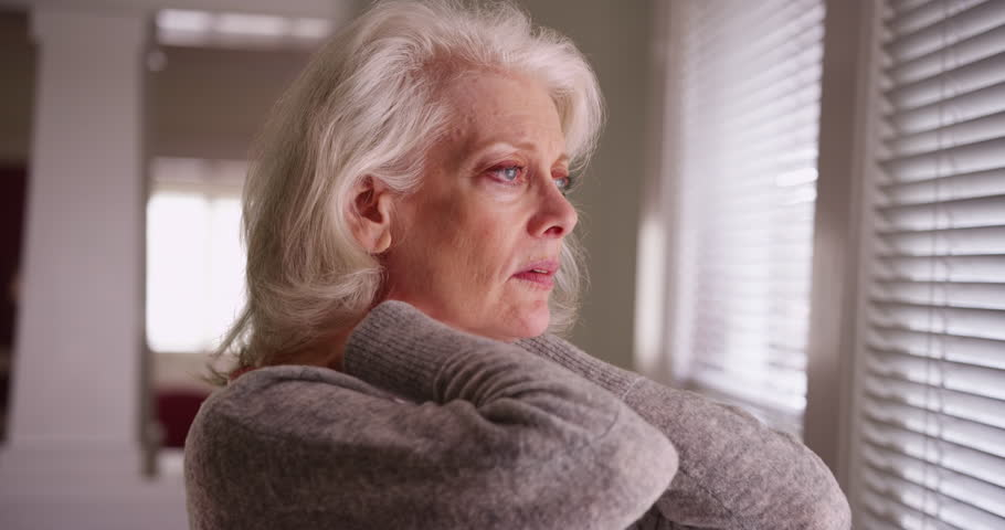 Close up of elder woman with sore neck looking out window. Close-up of mature woman in her 50s with chronic neck pain looking worried. 4k | Shutterstock HD Video #31489291