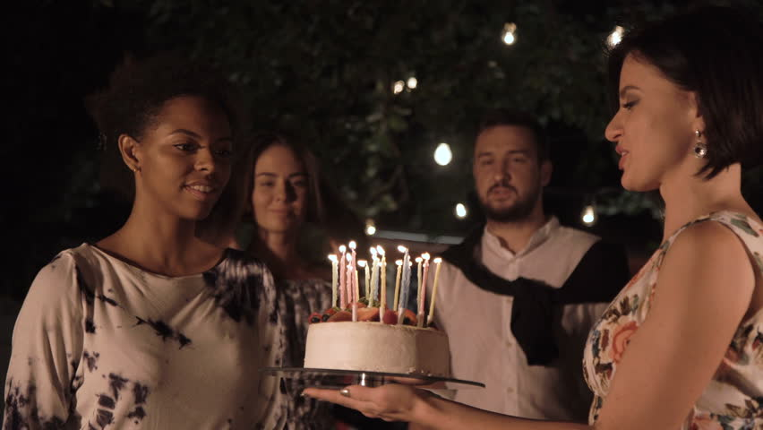 Cheerful Black Women Celebrating With Cake And Blowing Candles On Backyard