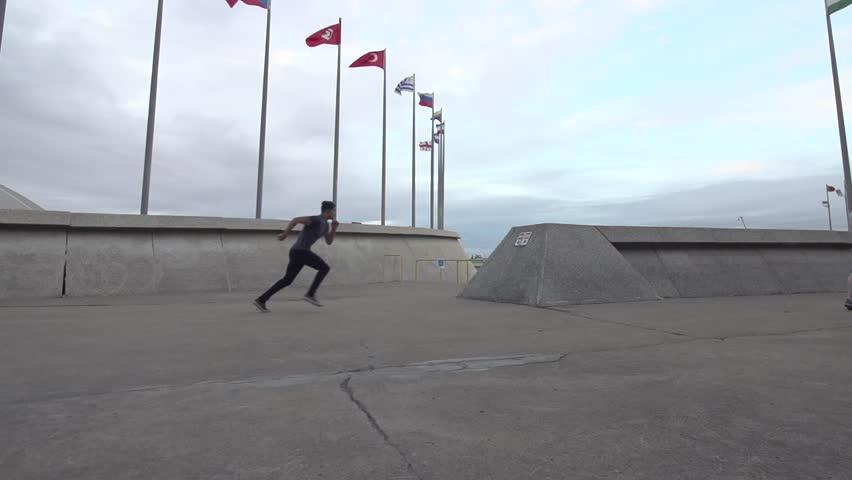 Parkour artist does elevator side flip up concrete structure and flip off. Shot in Sow Motion