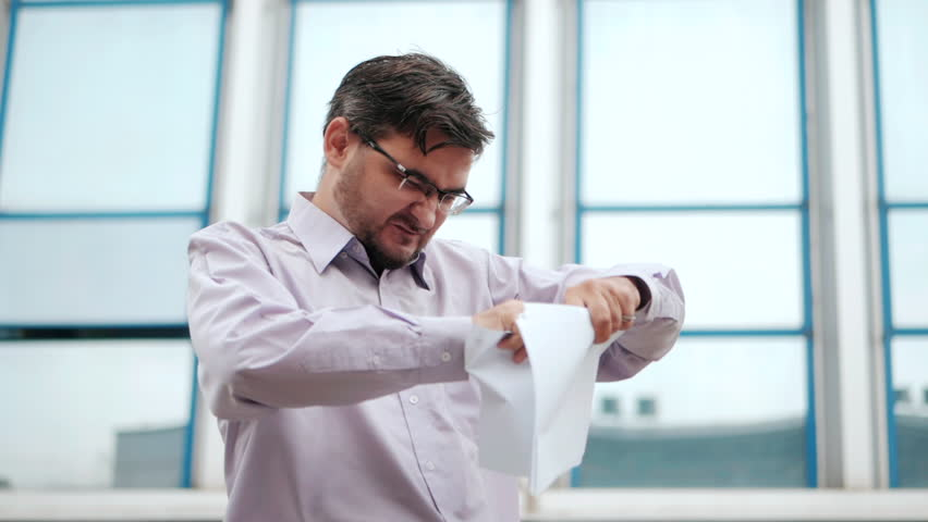 Slow motion of a serious businessman tearing a contract in pieces. Angry furious male office worker throwing crumpled paper, having nervous breakdown at work, screaming in anger, stress management