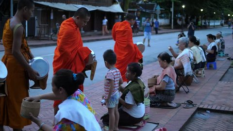 Buddhist Philanthropy Concept. Buddhist Monks Line Up in Row Waiting for Buddhism People to Give Alms Bowl in Thai Temple at Morning Time. Luang Prabang, Laos, 23 August, 2017. HD, 1920x1080.