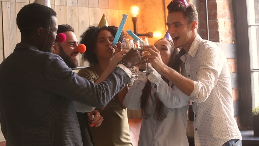 Multicultural young people in party hats clinking glasses celebrating holiday, diverse friends hanging out having fun holding champagne blowing party whistles at new years eve celebration indoors | Shutterstock HD Video #31517581