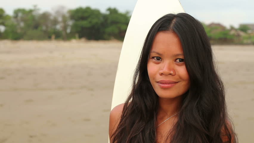 Portrait of smiling female surfer on beach with her surfboard