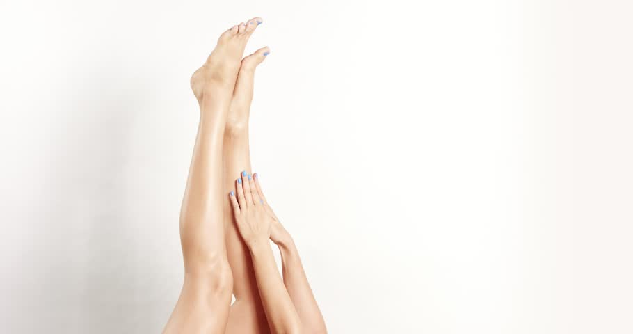 Close up of young beautiful woman with her legs in the air massaging legs with her hands with blue nail polish isolated on white