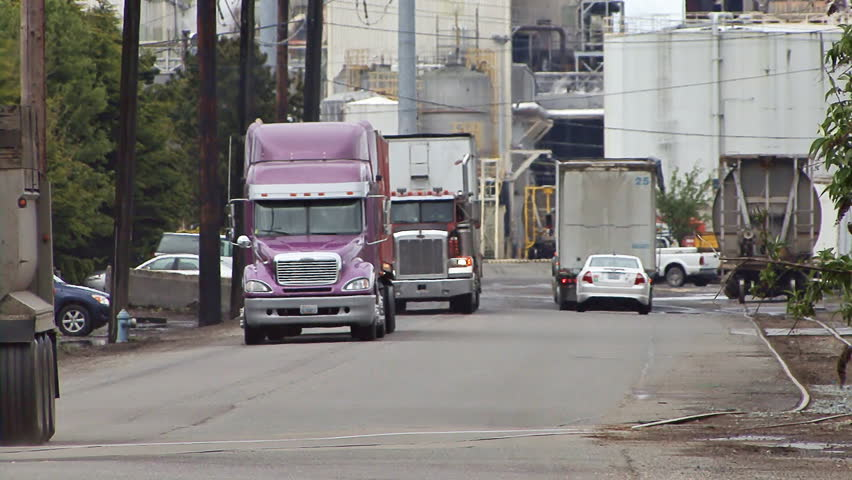 TACOMA, WA - CIRCA 2012:Trucks hauling materials and goods out of and through a busy industrial mill complex.