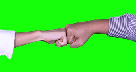 Team work concept: Closeup of unknown two business people hands giving secret handshake /fist bump. Shot in 4k resolution with green screen background
