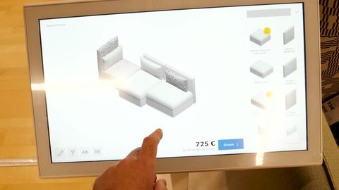 PARIS, FRANCE - CIRCA 2017: Virtual Reality furniture composition modular parts on touchscreen ikea shop - male had touching the VR screen select furniture parts, colors, garment, linen