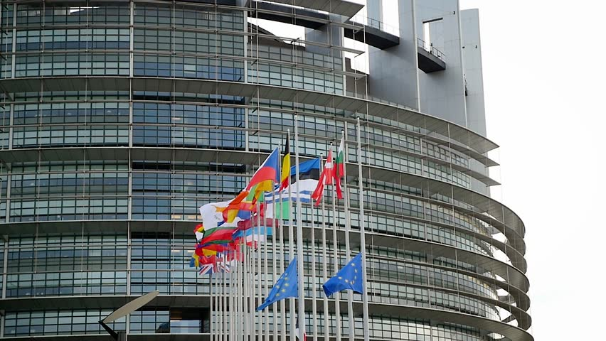 European Union Flag and France flag flies at half-mast in front of the European Parliament building following an terrorist attack in Paris - slow motion | Shutterstock HD Video #31564741