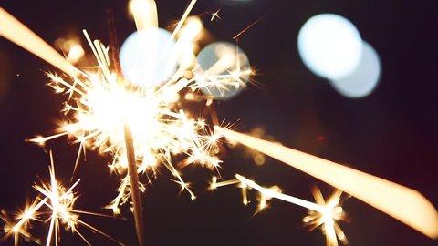 Firework sparkler burning with lights in background
