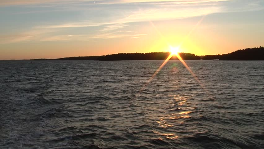 Finland, Aland, Houtskar: sunset over the sea. The sun sets behind the island. - HD stock video clip