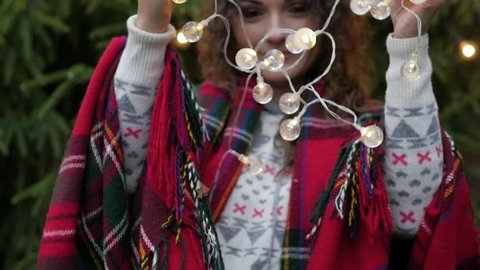 Christmas garland in the hands of a young woman on the background of the Christmas tree