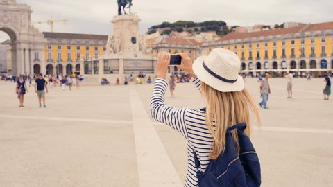 Woman tourist with her phone camera in hands shooting in Lisbon,Portugal undersunlight and blue sky. Famous popular touristic place in the world, 4K