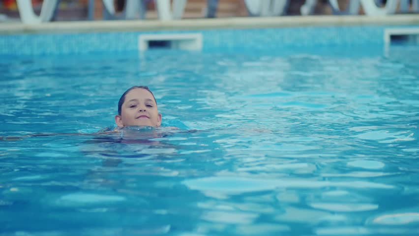 the girl is swimming in the pool