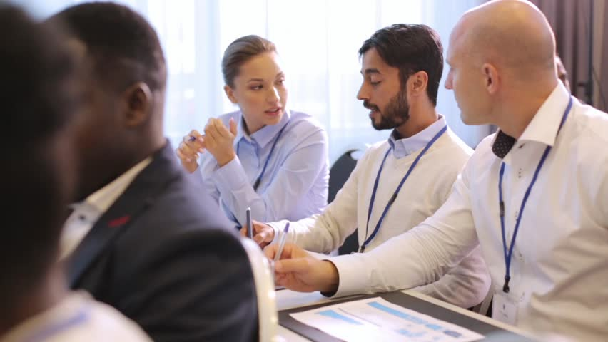 Business, people and education concept - businessman and businesswoman at international conference discussing papers | Shutterstock HD Video #31607314
