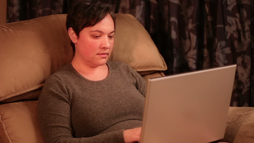 A woman uses a laptop while sitting in a recliner.
