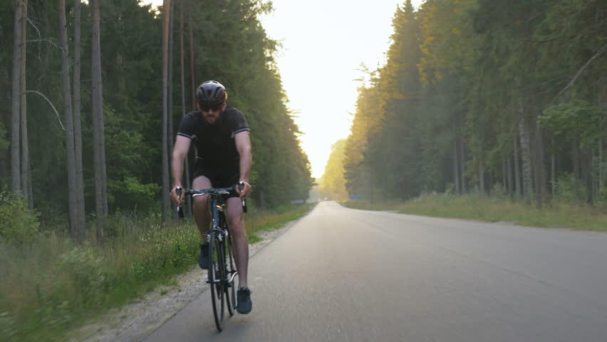 Healthy Man Doing Fitness Workout On A Bike Outdoors Tracking Shot Of An Energetic Male