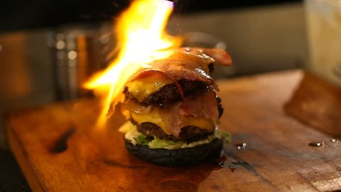Cook uses a blow torch on a burger.