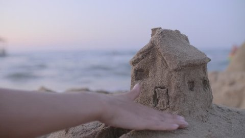 Small house with a roof made of sand on the beach at sunset. Property insurance, house protection or saving and security concept. Home under woman's care. Protecting gesture of young girl.