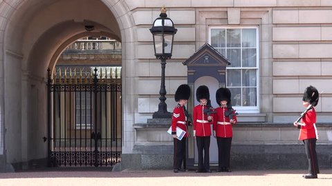 LONDON, ENGLAND, UK - AUGUST 13, 2017: Change of guards at Buckingham Palace. Infantry sentries of Queen's Guard respect a strict protocol when switching the shifts