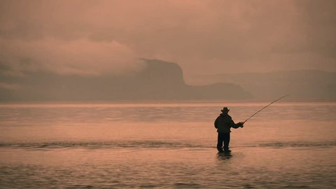 NEW ZEALAND - TAUPO - A fly-fisherman attempts to catch trout at the mouth of the Hinemaiaia Stream as it flows into Lake Taupo at sunrise/sunset.