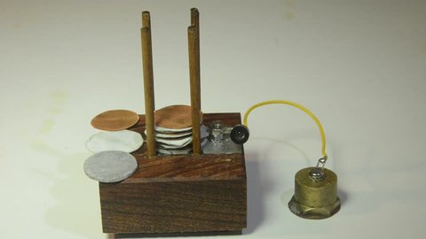 Assembly of a Voltage Column with plates of zinc, copper and electrolyte. Some elements have already been assembled. The column makes power for a LED light. Model of first battery discovered by Volta.