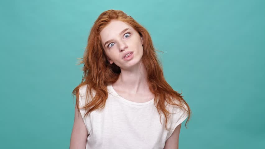 Happy funny ginger woman in t-shirt showing grimaces at camera over turquoise background