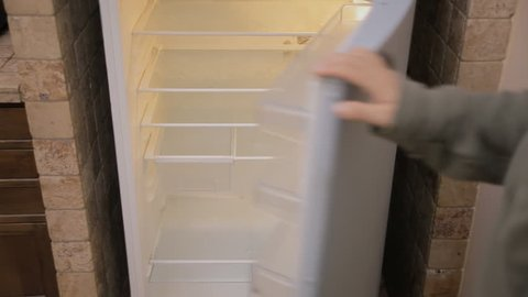 A man opening the fridge's door and finding nothing (it's completely empty), then closing it. Medium above shot, soft light.