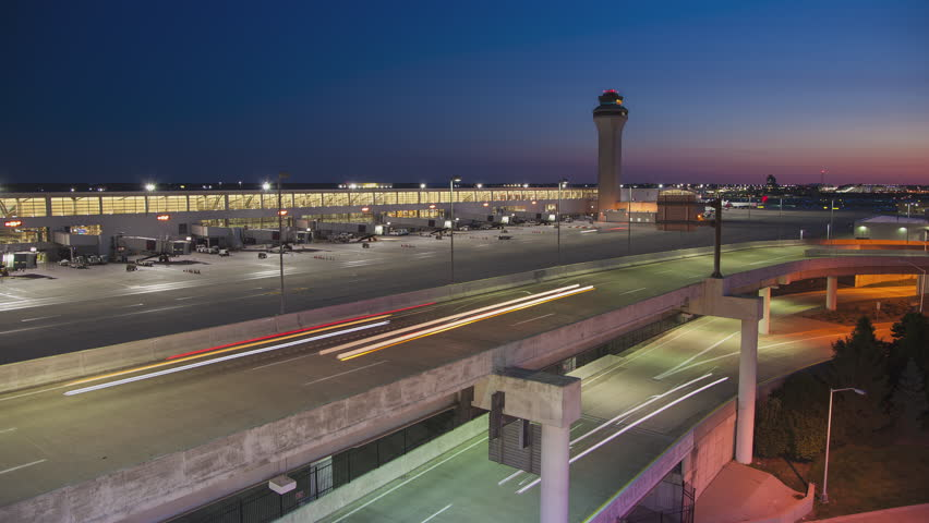 Early Morning Generic Airport Timelapse near City of Detroit with Arriving Vehicle Traffic Light Streaks from Driving Cars and the Air Control Tower in a Vibrant Colorful Sky