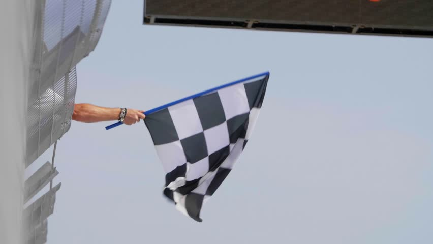 Man holding and waving Checkered race flag in slow motion at finish line on a raceway. Victory, achievement, success and sport concept.